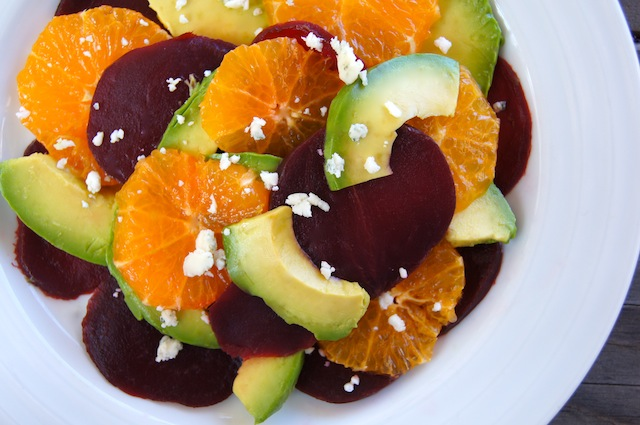 Beet and Aocado Salad with Pixie Tangerines on a bright white plate with bits of cheese sprinkled on top.