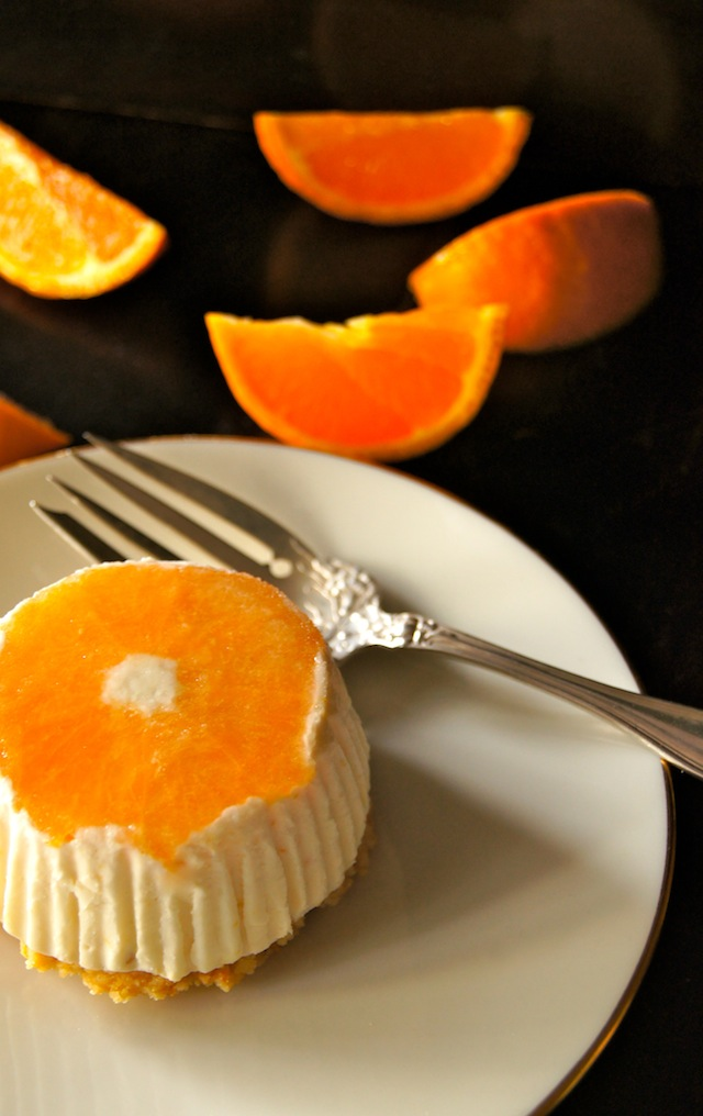 No-Bake Tangerine Cheesecake Recipe in an individual portion, on a cream plate with an antique silver fork.
