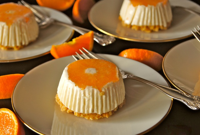 3 Individual portions of No-Bake Tangerine Cheesecake Recipe on cream plates with silver forks.