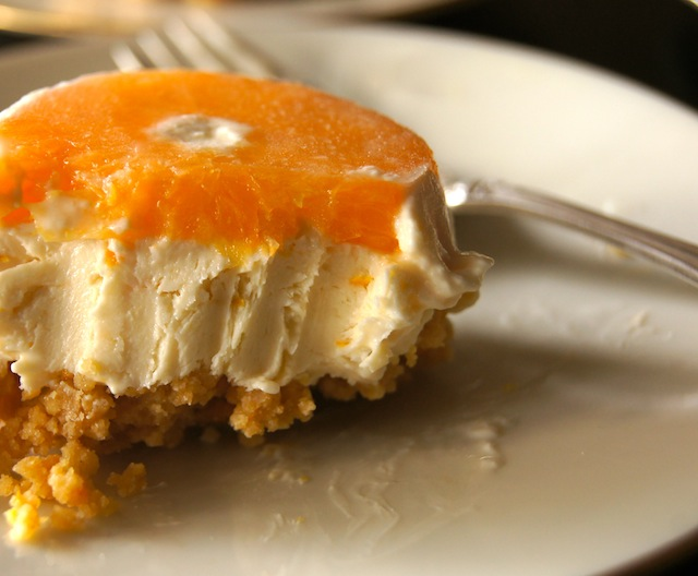 One individual No-Bake Tangerine Cheesecake Recipe with a couple of bites taken out of it, on a cream plate with silver fork.