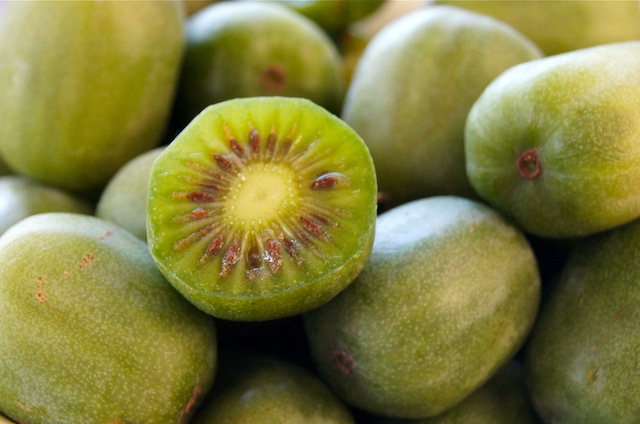 a pile of Baby Kiwi fruit with one sliced in half.