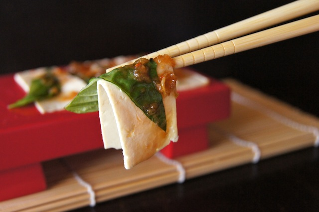 Tofu Sashimi on a red tray and one slice being held up with chopsticks.