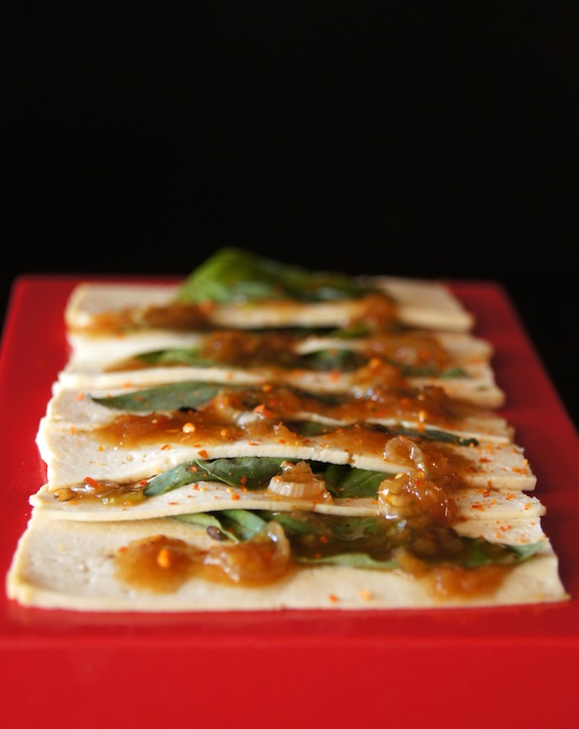 Tofu Sashimi with absil leaves lined up on a small red platter.