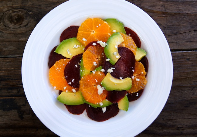 Beautifully composed Avocado Beet and Pixie Tangerine Salad on a bright white plate.