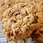 close up of an oatmeal raisin chocolate chip cookie on a cooling rack