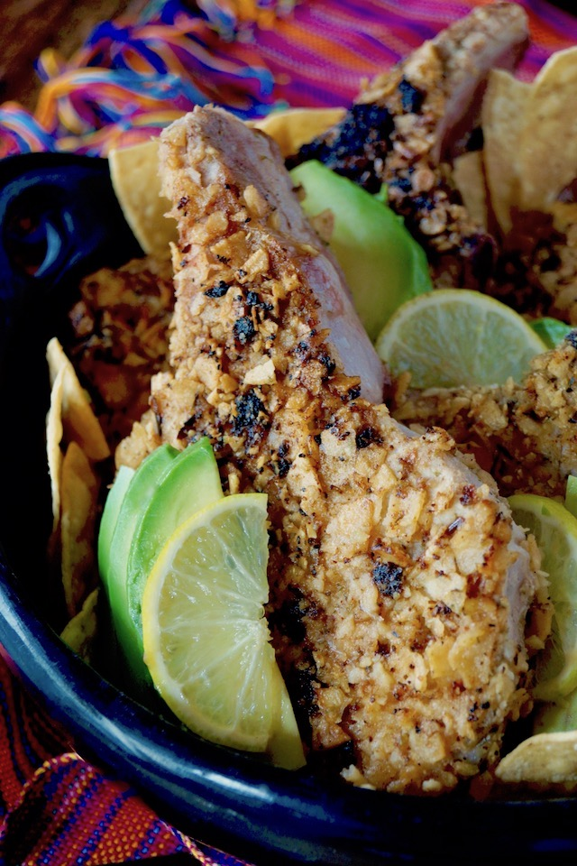 Tortilla Chip Crusted Prok Chop with avocado and lime slices.