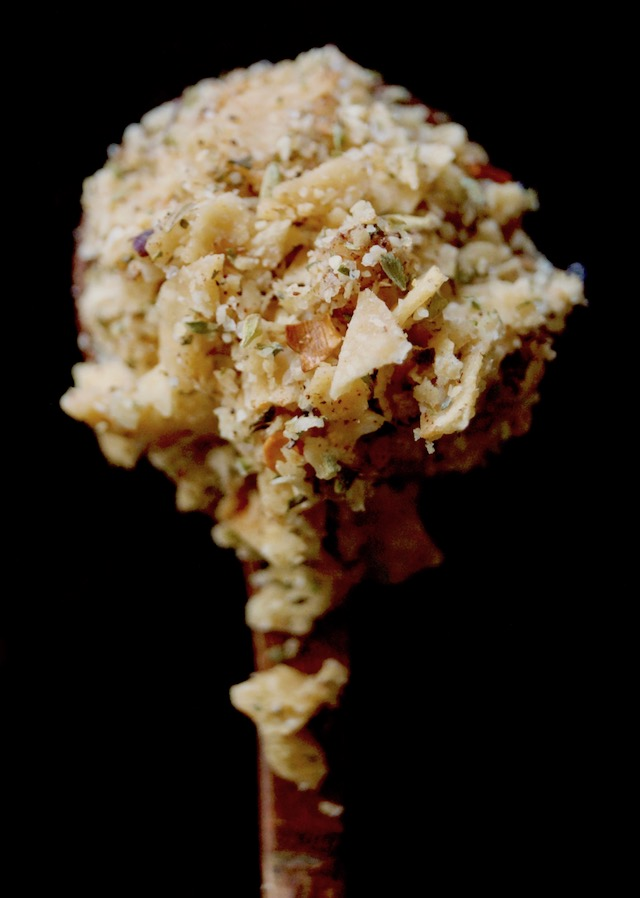 Wooden spoonful of crushed tortilla chips mixed iwth spices