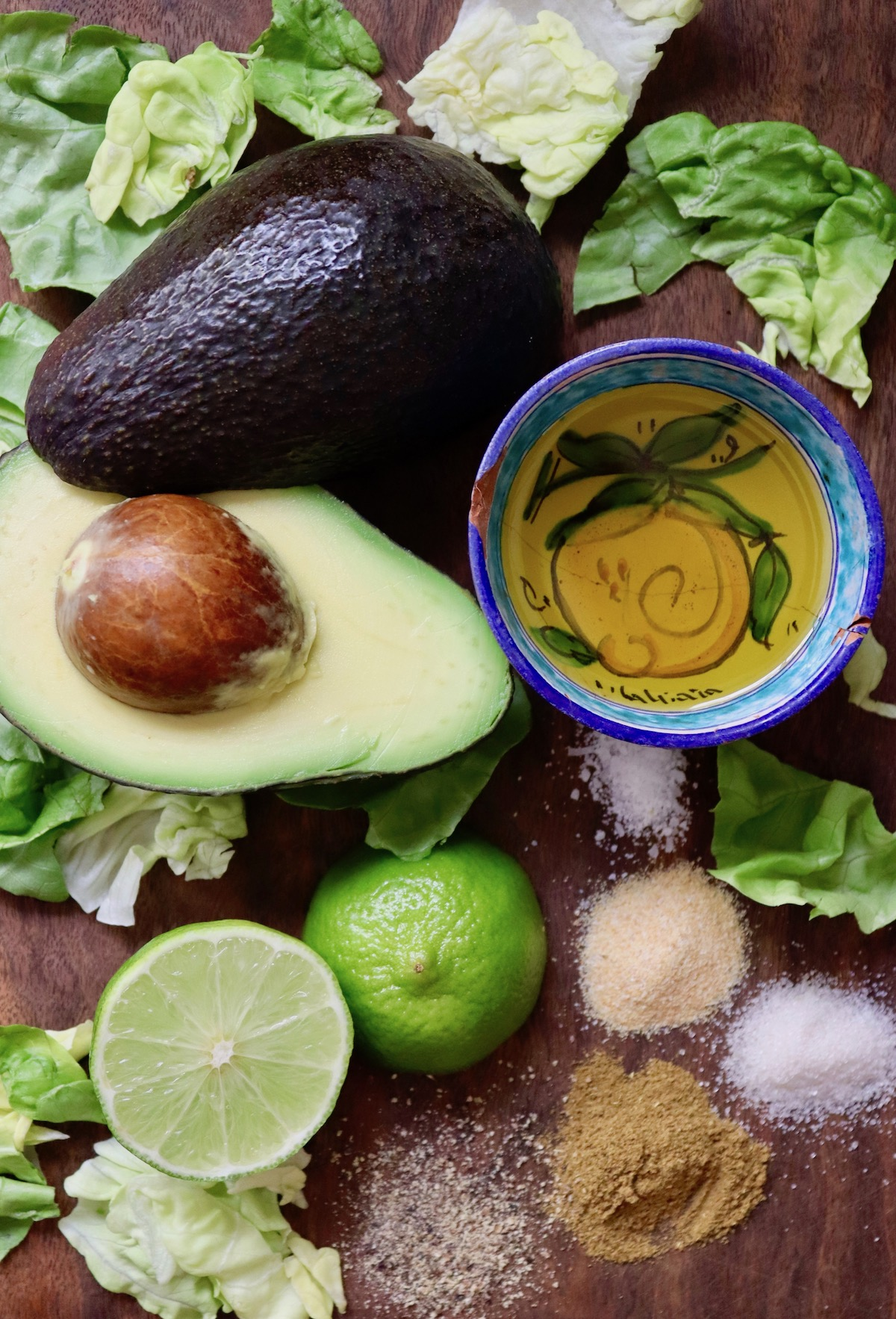 Creamy Lemon-Lime Avocado Dressing drizzled over lettuce greens on a red plate.
