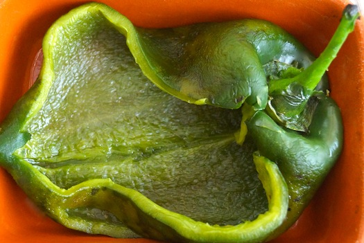 1 roasted poblano pepper sliced open in a teracotta dish