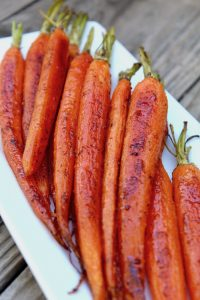 Baby carrots roasted with honey and cardamom on white plate
