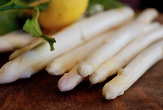raw white asparagus spears with a lemon