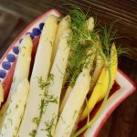 close up of white asparagus with lemon and dill