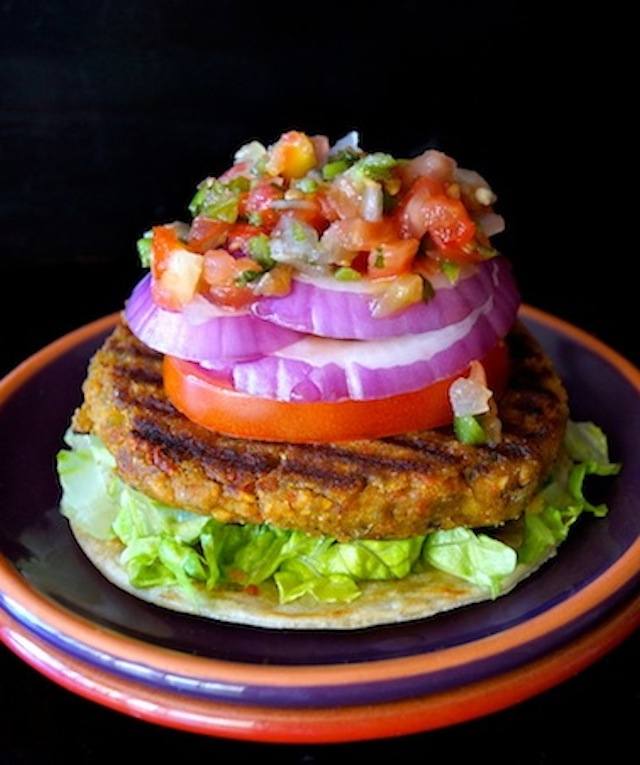 Vegan Yellow Split Pea Burger with lettuce, tomato, red onion and salsa, on a dark purple and red plate.