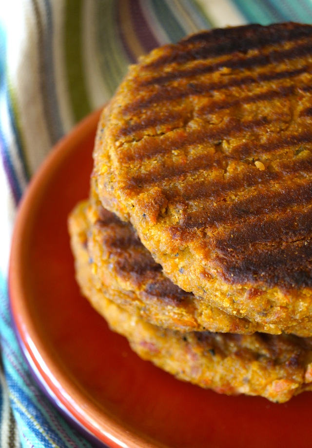 Stack of Grilled Split Pea Vegetarian Burgers on a red plate.