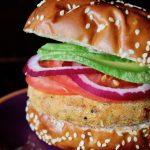 yellow split pea burger in pretzel bun with tomato and avocado