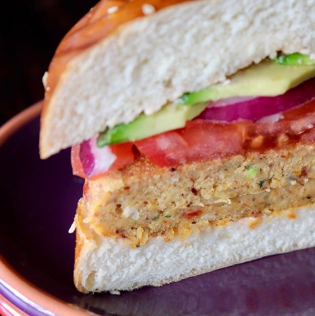 veggie burger in pretzel bun with tomato and avocado, cut in half