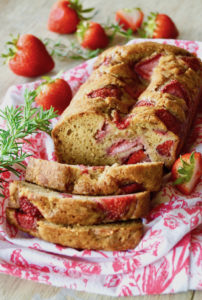 Sliced Strawbery-Rosemary Cake on a white and pink cloth with fresh rosemary sprigs and whole strawberries in background.