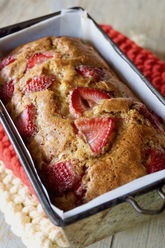 Baked Rosemary-Strawberry Cake in loaf pan, right out of oven on hot pads.