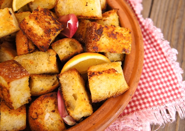 Marinated Lemon Garlic Roasted Croutons in a round terracotta bowl with red-skinned garlic cloves and a lemon wedge.
