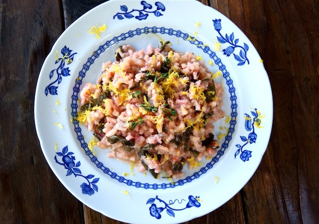 Meyer Lemon Red Chard Risotto With Pancetta in a white bowl with blue flowers along the edges.