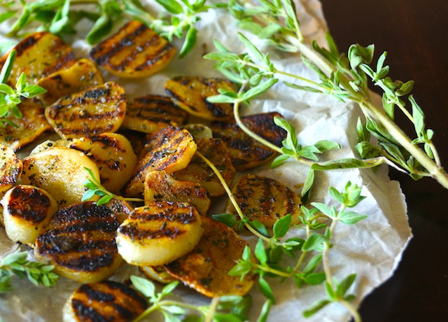 Herb Grilled Elephant Garlic with fresh thyme on parchment paper.