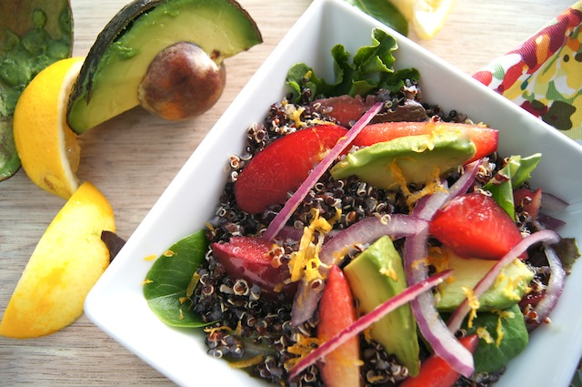 Lemon Black Quinoa-Plum & Avocado Salad in a square white dish, surrounded with lemon wedges and avocado half with pit.