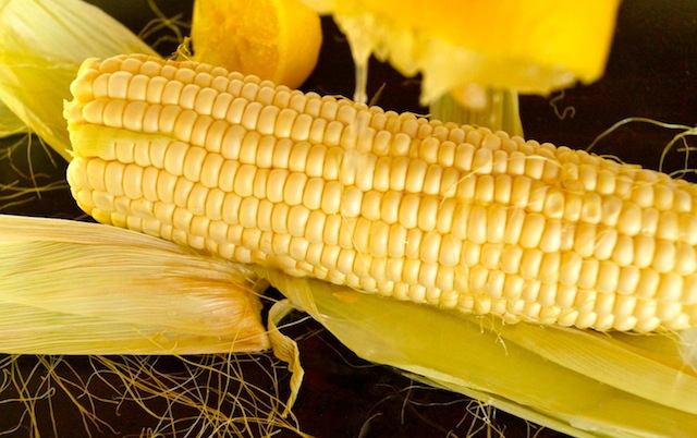 One ear of corn with lemon juice dripping onto it from above.
