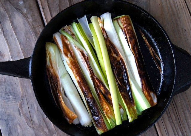 Lemon Sherry Braised Leeks in a cast iron skillet on a wooden table.