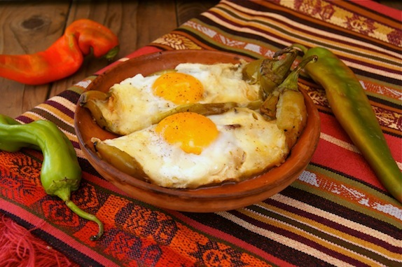 Hatch Chile Pepper Jack Bacon and Eggs in a teracotta bowl on a Mexican-style tablecloth.