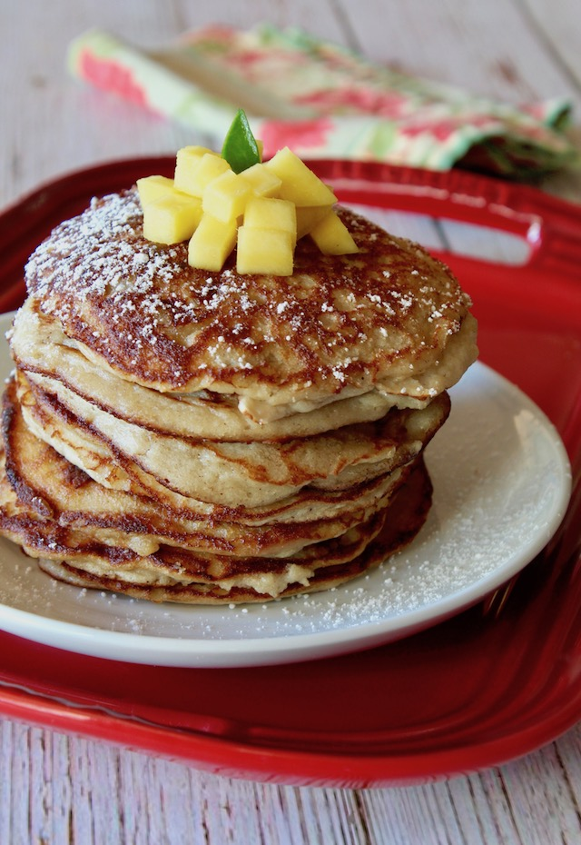 Tall stack of coconut flour pancakes on a whitle place iwth mango on top