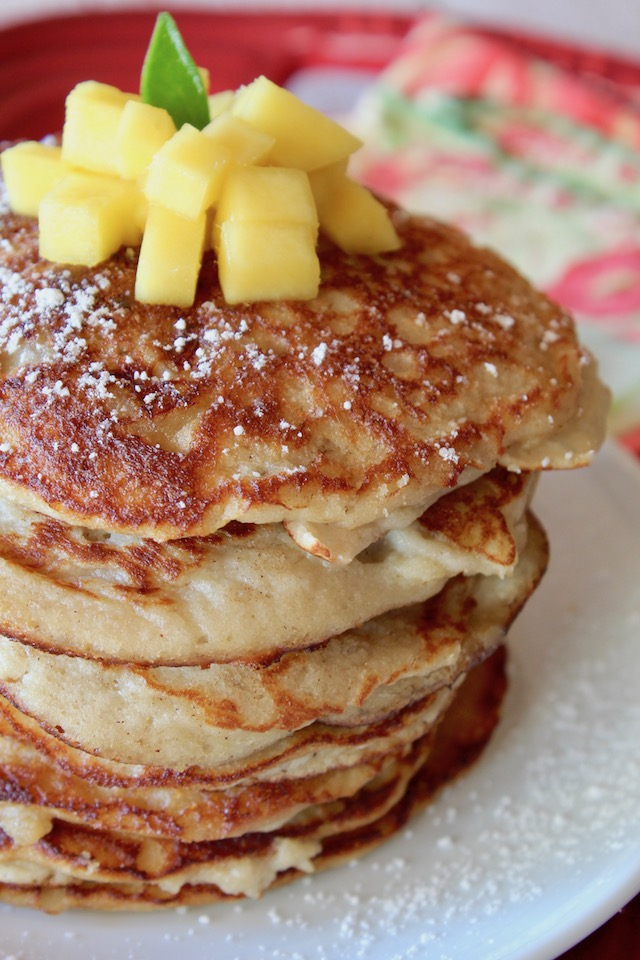 close up of a stack of gluten-free coconut flour pancakes with cut mango on top