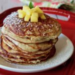 stack of coconut flour pancakes on a whitle place iwth mango on top