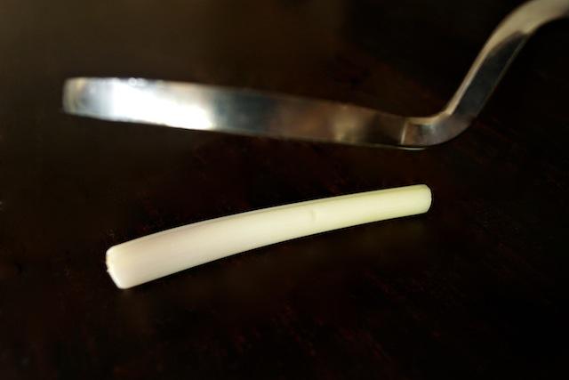 meat mallet above white stalk of lemongrass