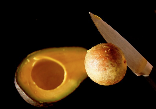 avocado half with pit above it attached to knife