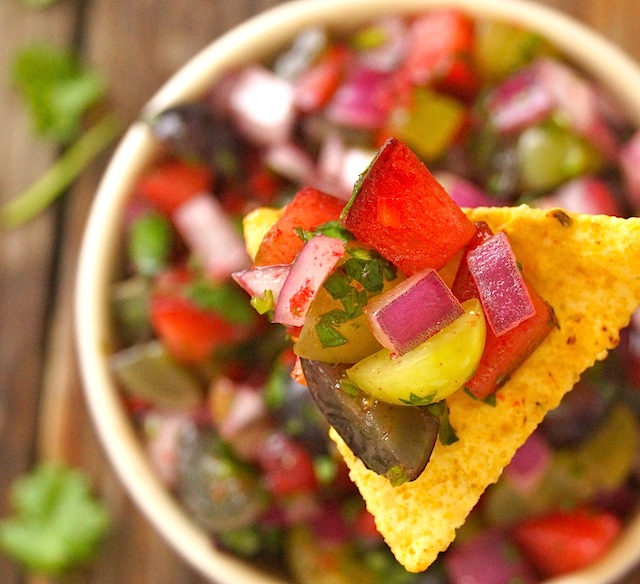Grape-Plum Summer Salsa on a chip above a bowl filled with it.
