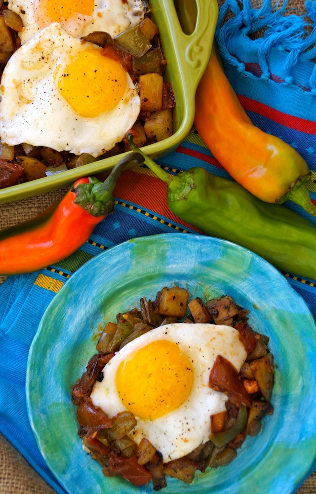 Hatch Chile Potato Hash and Eggs with Chipotle Roasted Tomatoes on a bright blue plate with a green baking dish with more behind it, and red Hatch Chiles.
