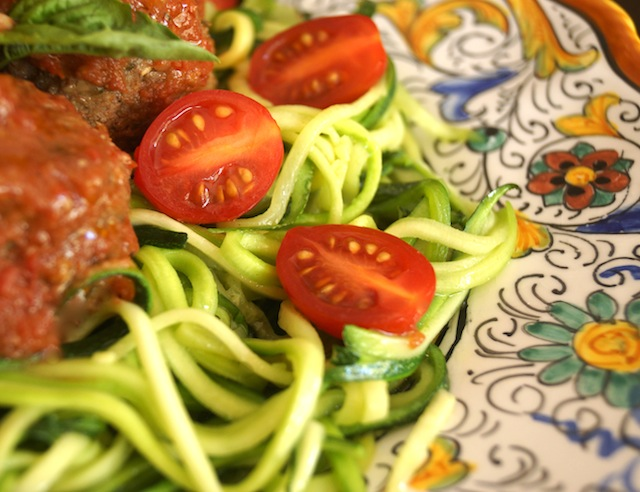 Close up of Zucchini Summer Spaghetti and Pesto Meatballs on an Italian-patterned platter with halved cherry tomatoes.