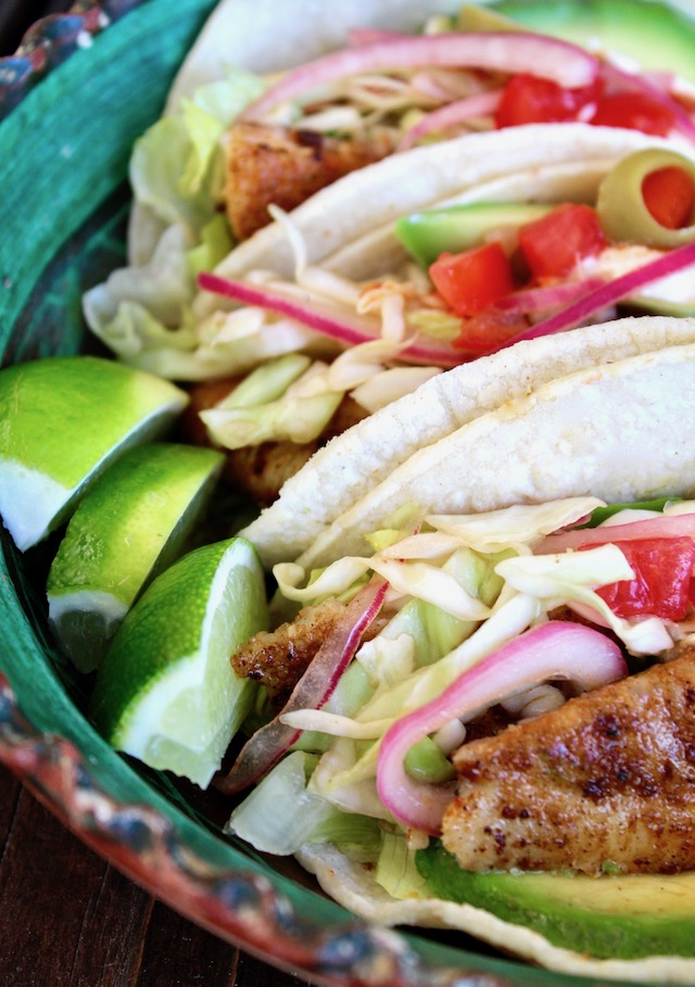 close up of fish tacos with 3 wedges of lime