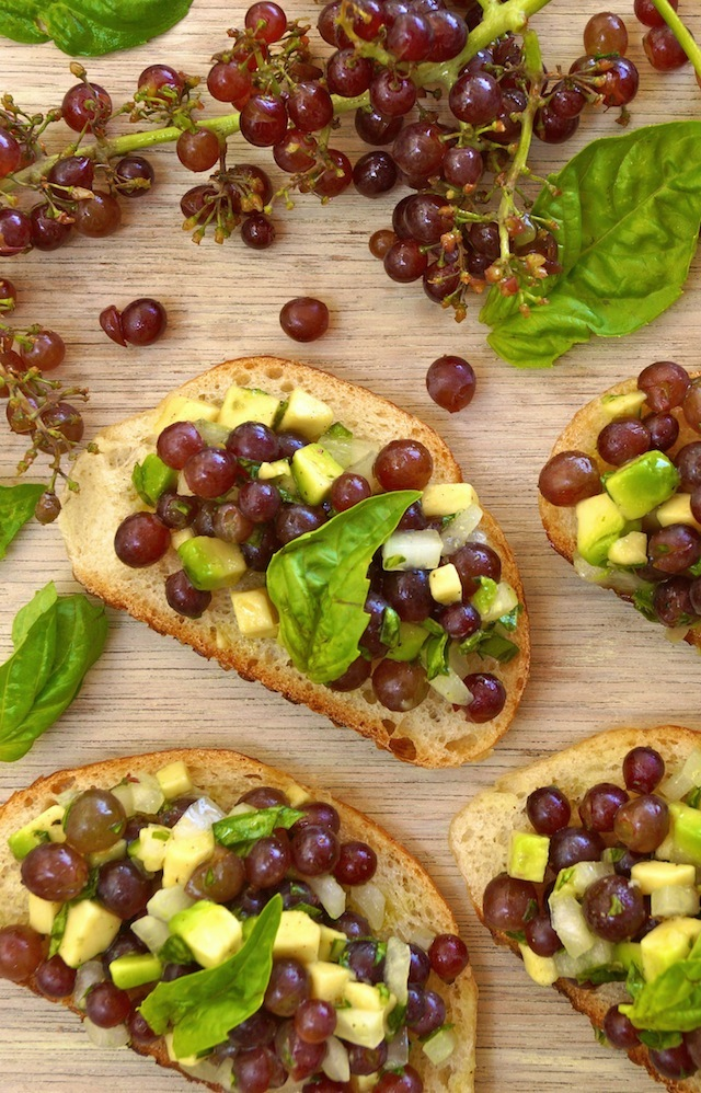 Bruschetta with Champagne Grapes on a light wood surface