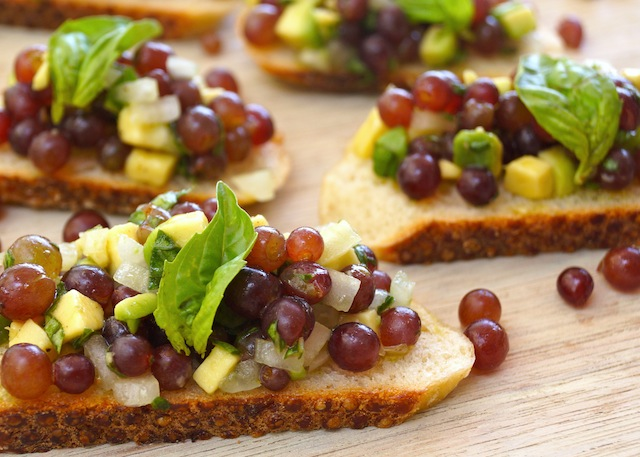 a few Bruschetta with Champagne Grapes on wood board with basil