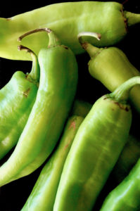 pile of bright green hatch chiles on black background