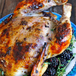 Whole roasted chicken on blue platter with blackberries