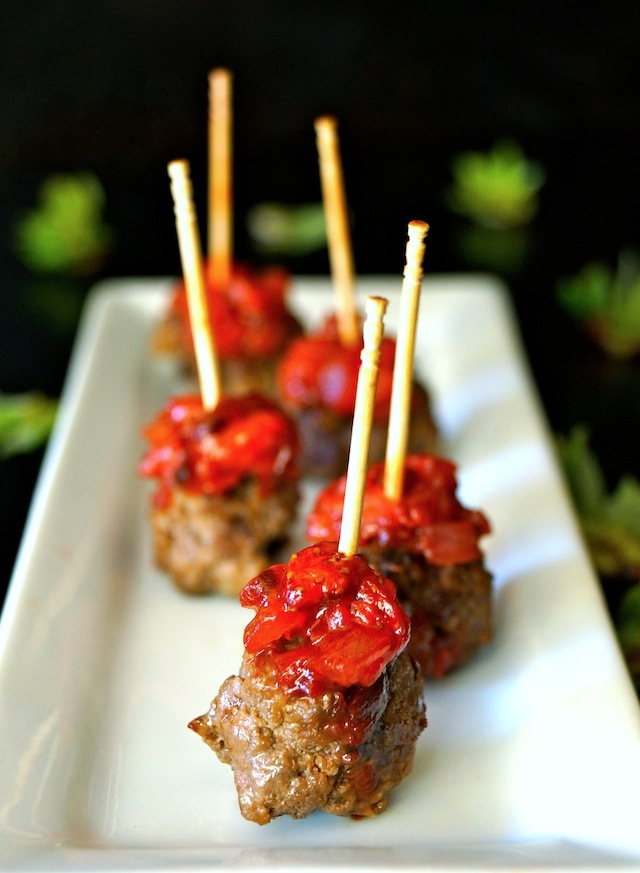 Strawberry Chipotle Bacon-Meatball Appetizer on a narrow white plate with toothpicks.