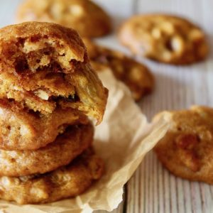 a few stacked pumpkin cookies on parchment paper