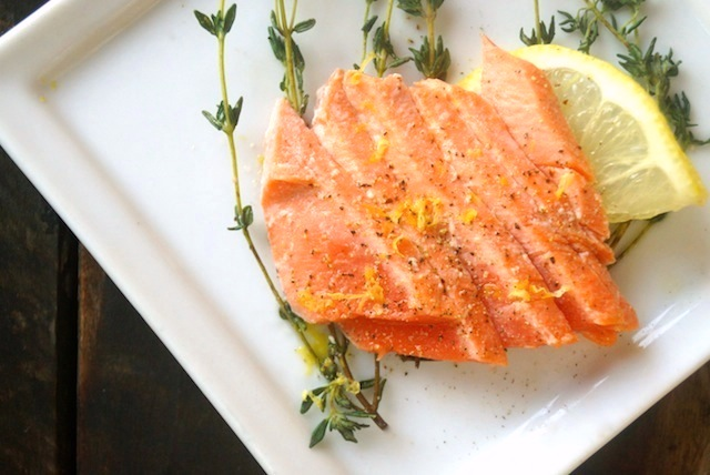 Olive Oil Poached Salmon on a white plate with lemon
