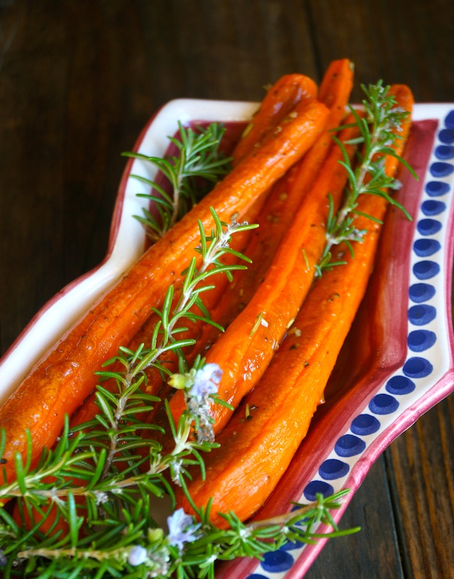 Herbs de Provence Roasted Carrots in a blue-polka-dotted dish with fresh rosemary.