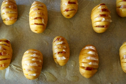 Baby Dutch Yellow Potatoes with many slits in them, with bacon in each one, on parchment