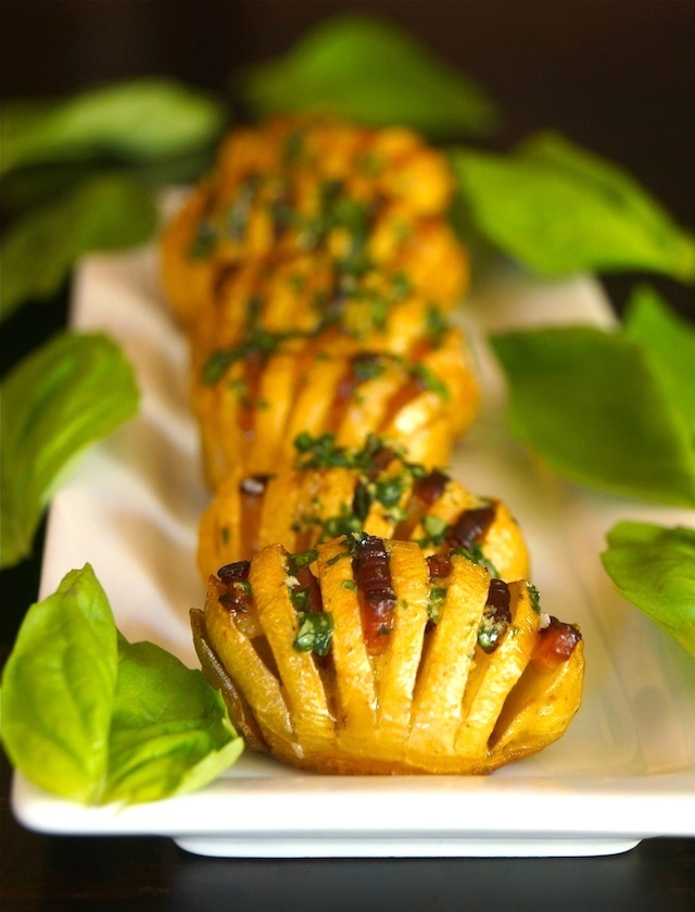 Several Bacon Basil Hasselback Dutch Yellow Potatoes on a long, white narrow plate surrounded with fresh basil leaves