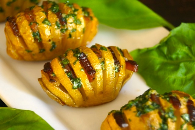 3 Bacon Basil Hasselback Dutch Yellow Potatoes on a white plate.