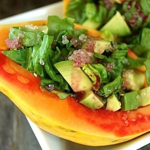 Papaya Avocado Salad with Cactus Pear Lemon Vinaigrette severed in half of a papaya on a white plate
